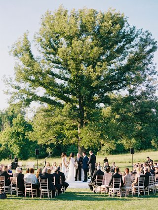 bride-and-groom-at-outdoor-wedding-ceremony-guests-seated-in-the-round-under-tall-tree