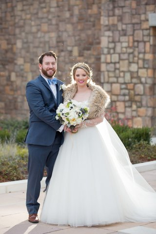 couple-winter-wedding-attire-embracing-navy-suit-ball-gown-bouquet-north-carolina-wedding-headpiece