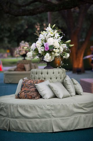 round-tufted-bench-in-light-green-with-flower-arrangement-with-hydrangea-lily-rose-flowers
