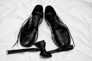 grooms-black-dress-shoes-and-bow-tie-on-white-sheet