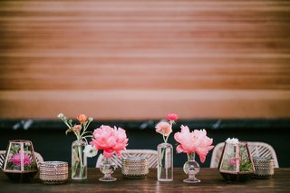 wedding-reception-decor-wood-background-bar-table-with-pink-peony-bud-vases-terrariums-rattan-chair
