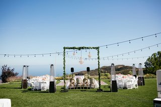 outdoor-reception-string-lights-greenery-arch