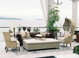 dark-leather-chesterfield-sofa-with-antique-armchairs-and-large-ottomans-lake-house-wedding