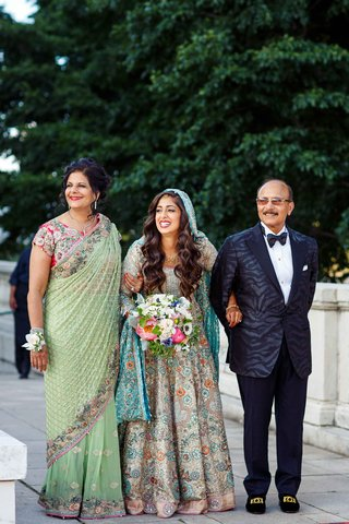 pakistani-bride-in-colorful-sleeved-gown-being-walked-down-the-aisle-by-her-mother-and-father