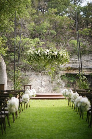 outdoor-wedding-ceremony-with-white-flowers-suspended-over-the-altar