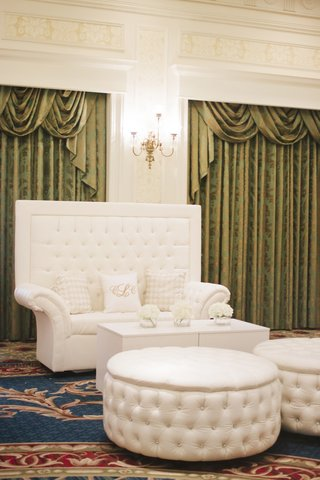 ballroom-wedding-lounge-with-tufted-white-settee-and-ottoman