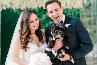 bride-and-groom-looking-at-little-black-dog-looking-lovingly-at-their-pup-wedding-day