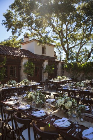 outdoor-wedding-reception-with-wood-tables-chairs-white-roses-hydrangeas-greenery-at-holman-ranc