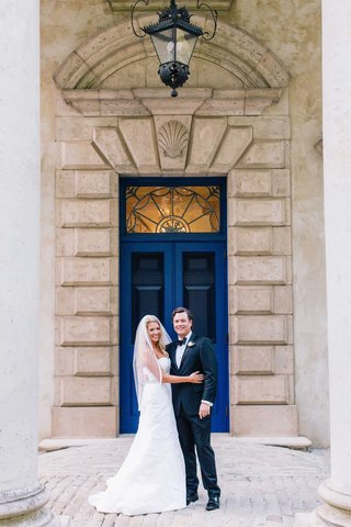 bride-in-anne-barge-wedding-dress-and-veil-and-groom-in-tuxedo-and-bow-tie-in-front-of-blue-door
