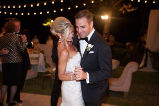 a-newlywed-bride-and-groom-dance-together-under-strings-of-lights-on-dance-floor-at-night