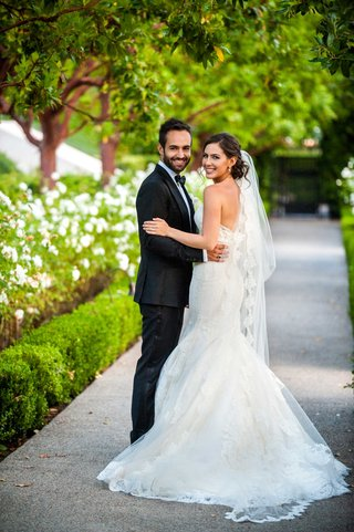 a-bride-and-groom-turn-back-to-camera-outdoor-space-to-smile-holding-each-other-ines-di-santo-dress
