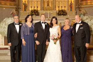 bride-and-groom-at-front-of-church-with-family-fathers-in-tuxedos-and-mothers-in-purple-hued-gowns