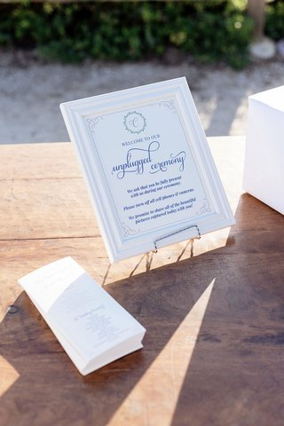 wood-table-with-ceremony-programs-and-unplugged-wedding-ceremony-sign-in-frame-on-stand