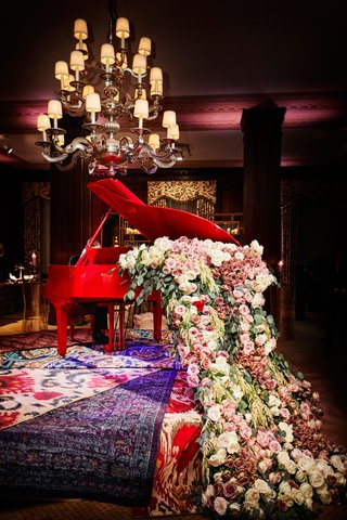 unique-wedding-decor-red-grand-piano-overflowing-with-pink-white-roses-and-greenery-layered-rugs