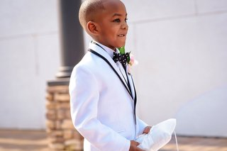 ring-bearer-walking-down-aisle-with-white-ring-pillow-polka-dot-bow-tie-white-jacket-suit