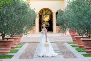 bride-standing-between-trees-in-strapless-dress