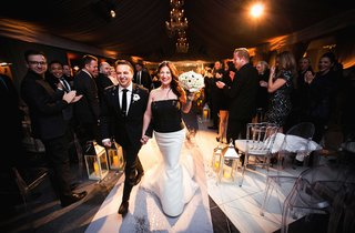 groom-in-black-tuxedo-and-bride-in-black-and-white-gown-walk-back-up-aisle-after-vows