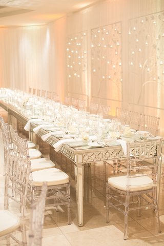 clear-chairs-around-mirror-dinner-table-at-modern-reception