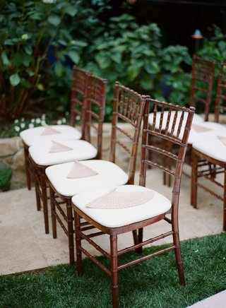 wedding-chairs-on-hotel-bel-air-swan-lake-lawn-with-wood-fans