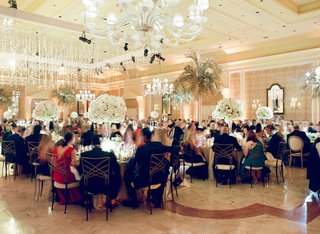 wedding-reception-guests-sitting-at-tables-palm-trees-chandeliers-ballroom-the-breakers