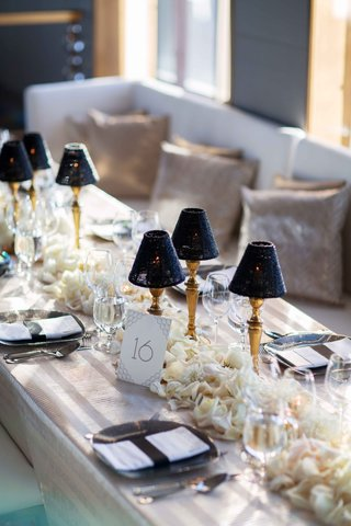 rainbow-room-wedding-reception-restaurant-flower-runner-gold-lamps-with-bead-lampshades-bench