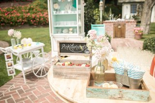 rustic-pink-lemonade-stand-with-strawberry-garnishes