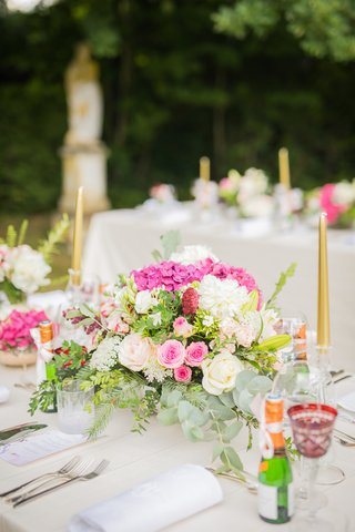 outdoor-wedding-reception-pink-and-white-flowers-gold-taper-candles-champagne-bottles-red-goblets