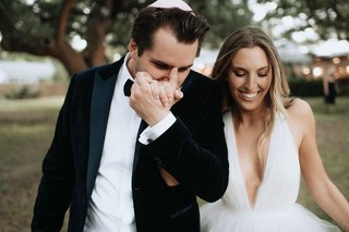 groom-in-tuxedo-bow-tie-yarmulke-kissing-wifes-hand-after-ceremony-v-neck-wedding-dress