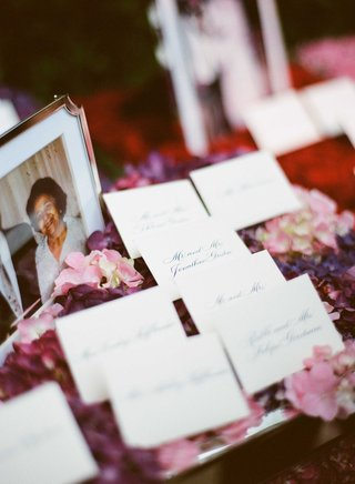 wedding-escort-cards-with-calligraphy-on-top-of-pink-and-purple-flowers-next-to-old-family-photos