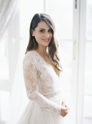 bride-in-monique-lhuillier-lace-long-sleeve-a-line-gown-brunette-hair-in-soft-waves-natural-makeup