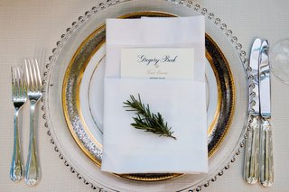 sprig-of-greenery-on-top-of-wedding-napkin-and-menu-on-charger-plate-place-setting