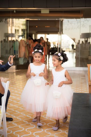 flower-girls-in-white-dresses-with-pink-tulle-skirts-flower-crowns-hair-up-updos-white-baskets