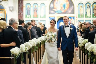 bride-in-monique-lhuillier-wedding-dress-groom-in-navy-tuxedo-bow-tie-flowers-white-hydrangea-on-pew