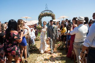 bride-in-ines-di-santo-wedding-dress-holding-grooms-hand-up-aisle-outdoor-summer-wedding-parasols