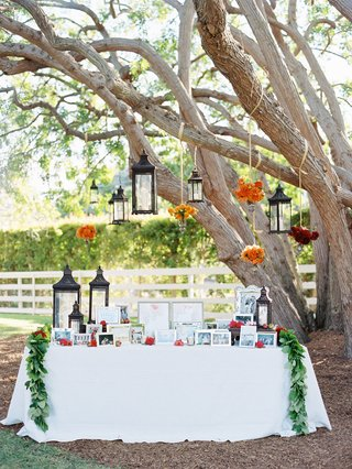 white-table-under-tree-with-moroccan-lanterns-and-flowers-at-photo-table