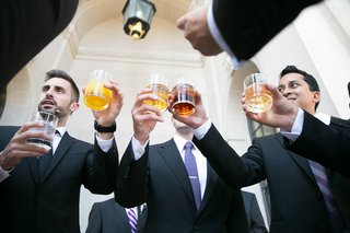 groomsmen-in-black-tuxedos-and-blue-or-purple-ties-say-cheers-with-drinks