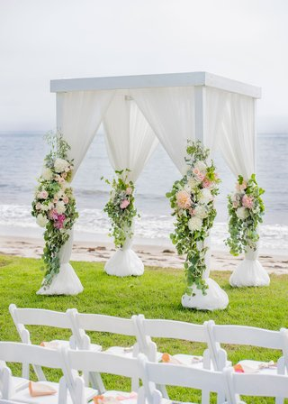 wedding-ceremony-on-grass-lawn-by-beach-ocean-white-drapery-greenery-peach-pink-flowers-dahlia-rose