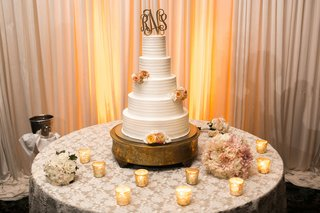 white-textured-wedding-cake-with-light-orange-roses-couples-golden-monogram