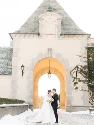 bride-in-ball-gown-with-white-fur-wrap-veil-low-bun-kiss-groom-in-arch-of-oheka-castle-snow-ground