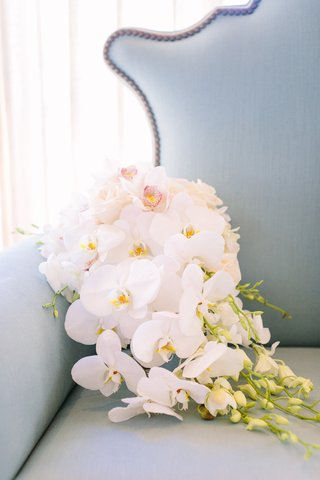 white-orchids-and-ivory-roses-with-cascading-greenery-on-blue-love-seat
