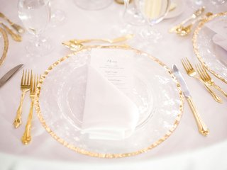 gilt-flatware-forks-and-knives-charger-plate-white-napkin-menu-on-white-tablecloth
