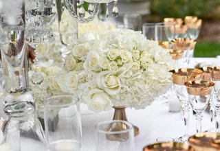 white-roses-and-hydrangeas-in-small-arrangement-held-by-gold-base