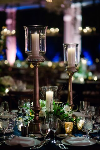 candles-displayed-on-candlestick-candle-in-hurricane-among-flowers-and-greenery