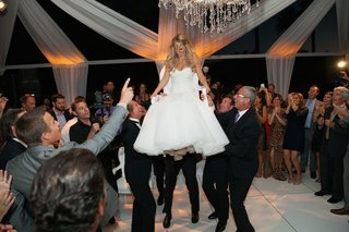 guests-in-formal-attire-lifting-bride-in-chair