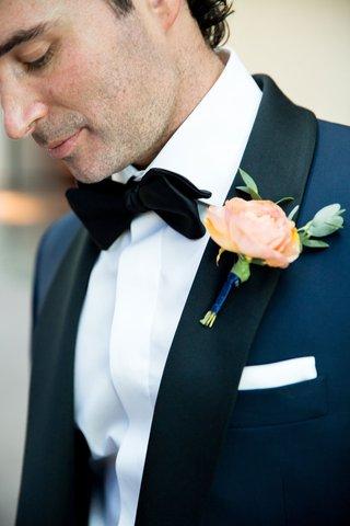 light-orange-flower-boutonneire-on-grooms-navy-blue-tuxedo-black-bow-tie