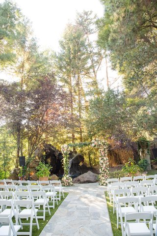 wedding-ceremony-stone-aisle-white-chairs-green-lawn-arch-with-fresh-flowers-tree-backdrop