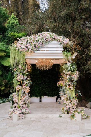 greenery-spilling-from-arch-at-hotel-bel-air-wedding-with-pink-roses-chandelier-garden-venue