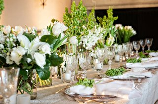 wedding-reception-greenery-and-white-flower-low-centerpieces-crystal-glassware-lily-tulip-flowers