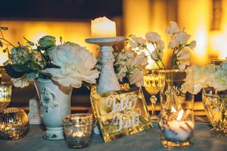 table-with-glass-vases-candle-stands-and-votives-and-white-flowers