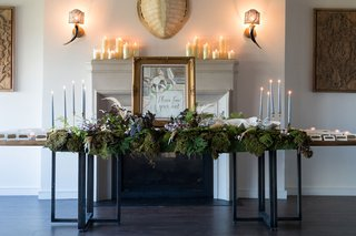 wedding-reception-escort-card-table-french-bulldog-painting-taper-candles-greenery-candles-fireplace